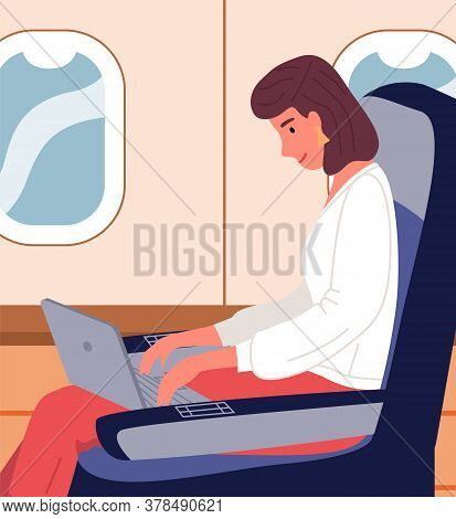 Businesswoman Sitting With Laptop In Business Class Of Airplane, Sitting Near Window, Using Internet
