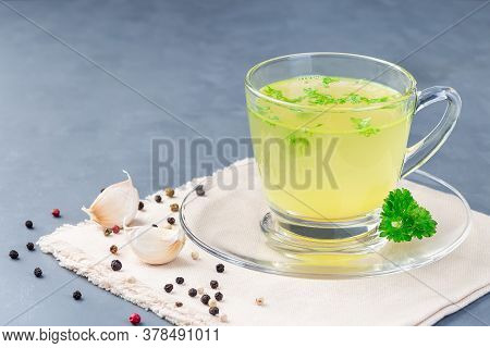 Chicken Broth In A Glass Cup With Chopped Parsley, Horizontal, Copy Space