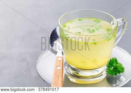 Chicken Broth In Glass Cup With Chopped Parsley, Horizontal, Copy Space