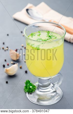 Chicken Broth In A Glass With Chopped Parsley, Vertical