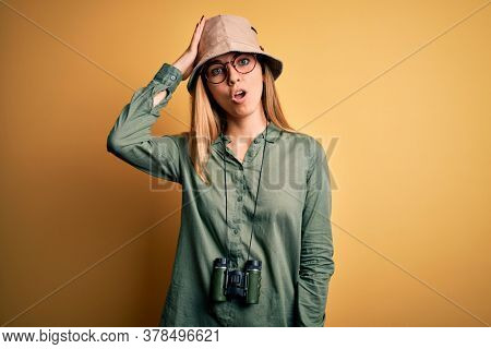 Beautiful blonde explorer woman with blue eyes wearing hat and glasses using binoculars surprised with hand on head for mistake, remember error. Forgot, bad memory concept.