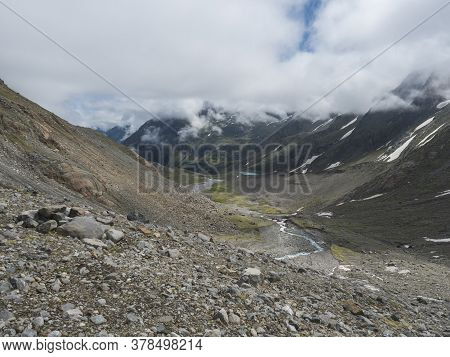 Summer View Of Alpine Mountain Valley With Winding Stream And Glacial Lake, Sulzenauferner Glacier,