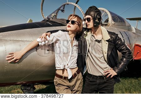 A beautiful girl and a handsome man pilots stand next to a fighter jet at the airfield. Military aircraft. Military fashion. Retro style.