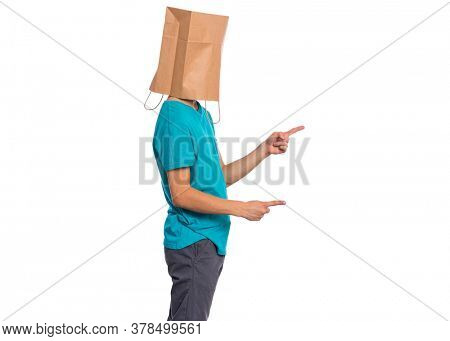 Portrait of teen boy with paper bag over head pointing hands away at copyspace - side view, isolated on white background. Child pointing finger at something - profile.