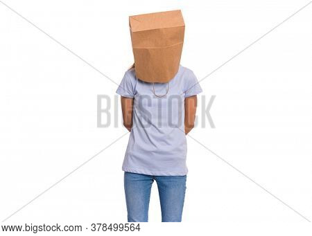 Portrait of teen girl with paper bag over her head, isolated on white background. Shy child pulling paper bag over her head. Teenager cover head with bag posing in studio.