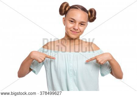 Portrait of teen girl pointing oneself, isolated on white background. Emotions and signs concept. Happy smiling child looking at camera. Young student points finger at himself.