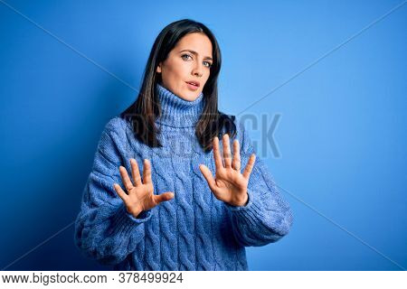 Young brunette woman with blue eyes wearing casual turtleneck sweater Moving away hands palms showing refusal and denial with afraid and disgusting expression. Stop and forbidden.