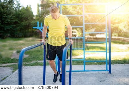 Man pulling up on parallel bars during street training