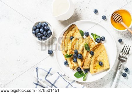 Crepes With Blueberries And Honey At White Stone Table. Top View With Copy Space.