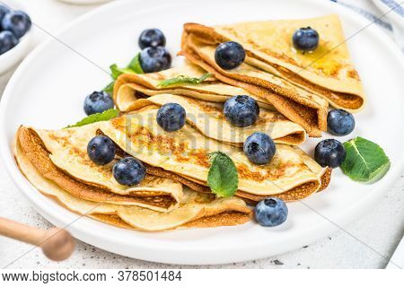 Crepes With Blueberries And Honey In White Plate.