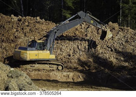 Yellow Excavator During Earthworks In An Open Pit Against The Background Of Forest And Soil. Constru