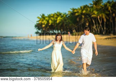 Happy Loving Couple In White Clothes Walking In The Water On The Sandy Beach. Honeymoon By The Sea O