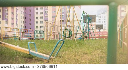 Empty Local Yard With Coloured Attractions Against City Buildings With Green Fence On Foreground On