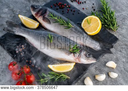 Fresh raw seabass with lemon tomato and spices on black stone plate with icy frost cold steam fog. Fresh food seafood at market concept.