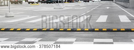 Striped Black And Yellow Speed Bump On Grey Asphalt Road With White Crosswalk Against Various Cars O