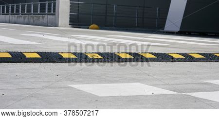 Black And Yellow Striped Rubber Speed Bump Located On Grey Road With White Marking Against Crosswalk
