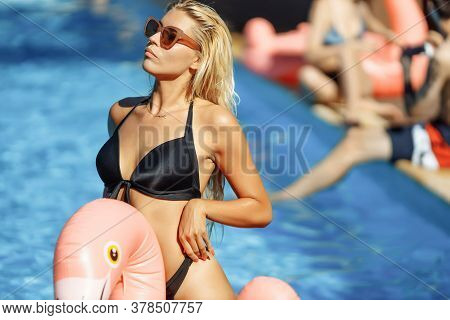 Young And Sexy Girl Having Fun And Laughing And Having Fun In The Pool On An Inflatable Pink Flaming