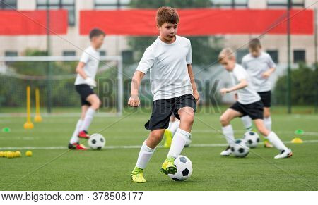 Children Kicking Soccer Balls On Artificial Grass Training Field. Young Boy Leading Ball And Improvi