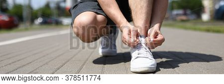 Close-up Of Man Tying Shoelaces On White Sneakers. Male Person Squatting On Sidewalk. Sunny Morning