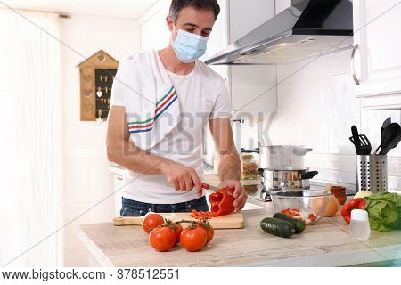 Man Preparing Vegetables To Make A Plate Of Food Confined By Covid-19 At Home With Mask
