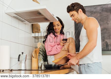 Selective Focus Of Smiling Girl Holding Glass Of Wine While Sitting On Worktop Near Boyfriend Cookin