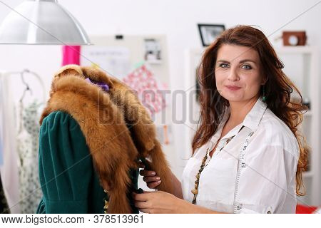Portrait Of Sewer Creating New Stylish Warm Coat With Natural Fur. Woman Looking At Camera And Smili