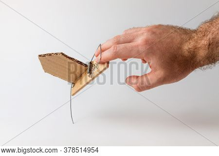 Bank Investments And Risks. A Mans Hand Caught In A Mousetrap With A Schematic Cardboard House. Copy
