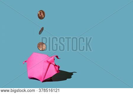 Pink Paper Piggy Bank And Three One Cent Coins Spinning In The Air On Blue Background, Hard Shadows.