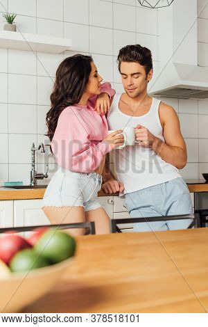 Selective Focus Of Young Couple With Cups Of Coffee Standing Near Worktop In Kitchen