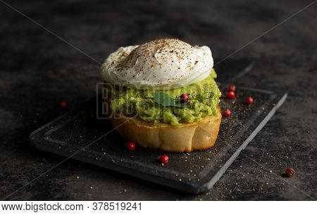 Poached Egg With Pink Peppercorns On Avocado Cream And Bread Toast On A Dark Background