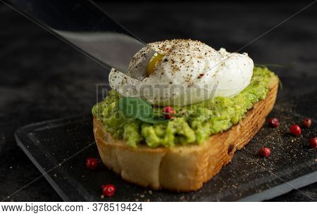 Knife Blade Cuts Poached Egg On Avocado Toast. Yolk On The Knife Blade.