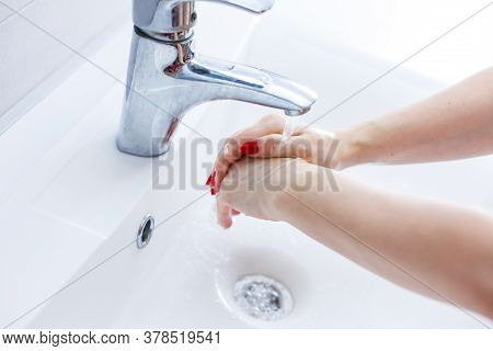 Washing Woman Hands With Streaming Water Under Tap In Bathroom, Washing Hands In A White Basin With