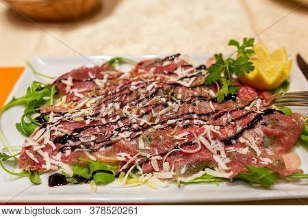 Meat Carpaccio. Thinly Sliced Raw Meat Carpaccio, Sprinkled With Parmesan Cheese With Parsley And Le
