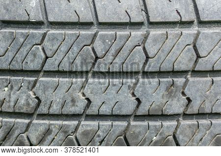 Used Car Tire In The Tire Repair Shop. Old Tyre In Auto Repair Service. Background Texture