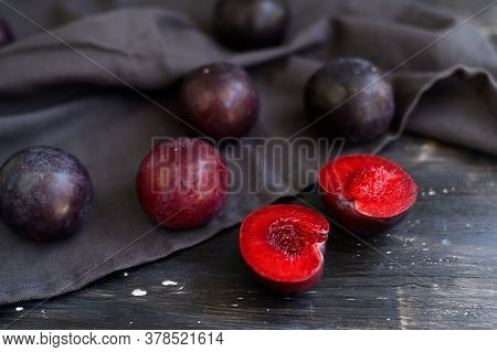 Ripe, Juicy Plums On A Black Wooden Background. Flat Lay.