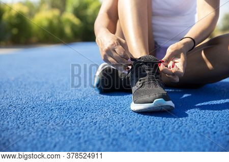 Close-up Of A Sportswoman Tying Her Shoe Laces Before Running. Space For Text. Selective Focus. Conc