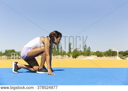 Young, Athletic Girl In Position To Start The Running Track Race Outdoors. Space For Text. Concept O