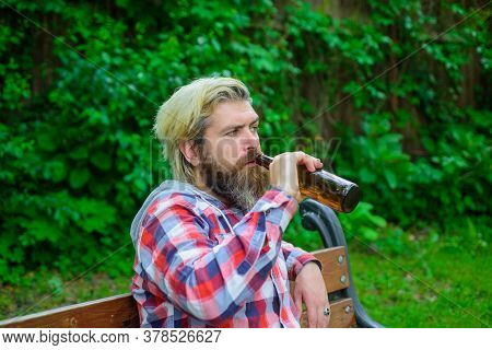 Handsome Bearded Male Dressed In Plaid Shirt Drinks Craft Bottled Beer. Bearded Man In Casual Clothe