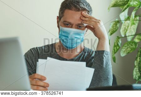 Man In Medical Mask Working With Papers In Office.