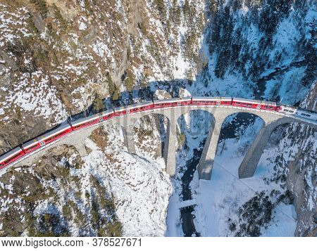 Filisur Switzerland - January 31. 2019: A Red Passenger Swiss Train Passing On The Famous Landwasser
