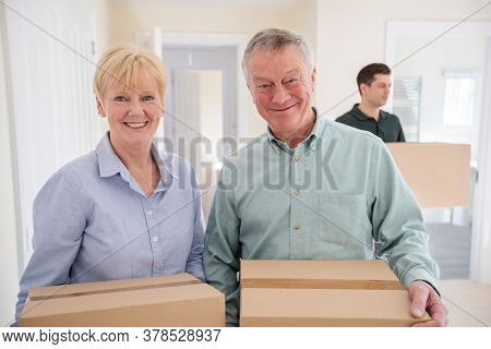Portrait Of Senior Couple Downsizing In Retirement Carrying Boxes Into New Home On Moving Day With R