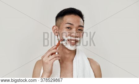 Shave Everyday. Portrait Of Young Asian Man With Towel Around His Neck Shaving His Face, Looking At