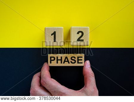 Businessman Holds A Block With Word 'phase'. Wooden Cubes With Numbers 1 And 2. Beautiful Yellow And