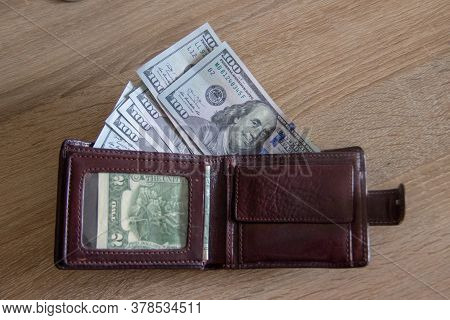 Stash In Your Wallet Just In Case. A Man Wallet Lies On The Table And One Hundred Dollar Bills Peep