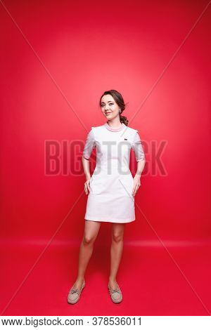 Attractive Woman Worker Of The Medical Field In Uniform Stands In The Studio Against The Background