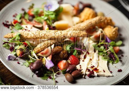 Cheese platter for two: Goat cheese cream, gorgonzola, camembert, grissini and fig jam. Delicious healthy Italian traditional food closeup served for lunch in modern gourmet cuisine restaurant.
