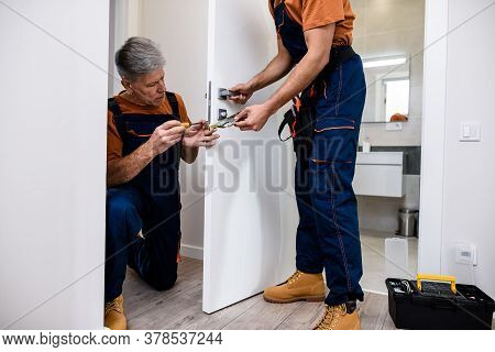 Aged Locksmith, Repairman, Worker In Uniform Installing, Working With House Door Lock Using Screwdri