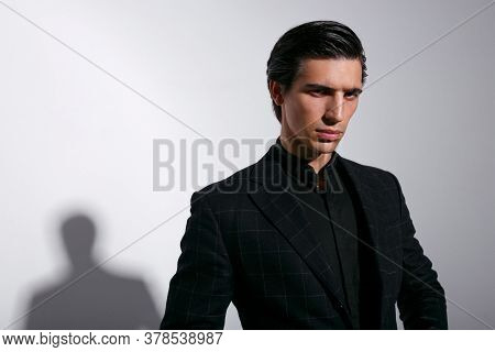 Frontal Portrait Of Confident Young Man In Black Suit Over White Background.