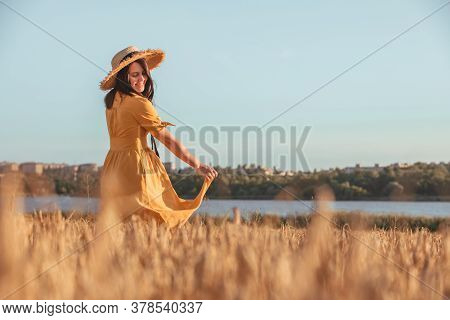 Woman In Yellow Sundress Walking By Wheat Field