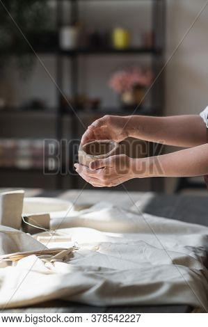 Close-up Of A Woman Potter Sculpts A Brown Clay Pot On The Background Of A Wooden Table In The Works